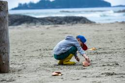 A child crouched down playing in the sand.